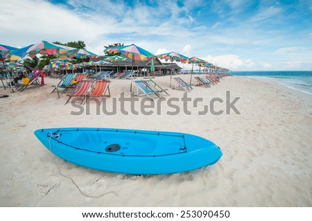 Canoe boat on the beach with seat and umbrella in the summer time - stock photo