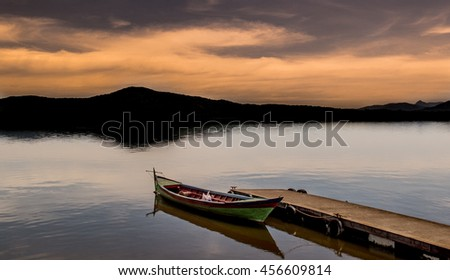 Canoe on Public Pier Under Beautiful Sunset on a Calm Lake