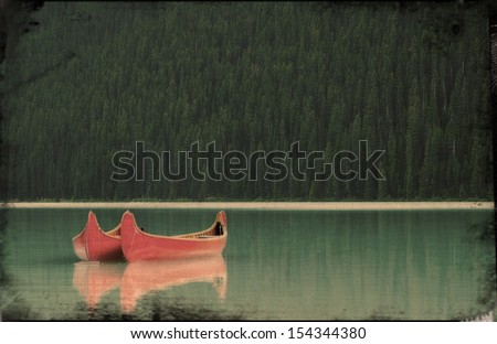 Canoes float peacefully on Lake Louise in Banff National Park, Canada. - stock photo
