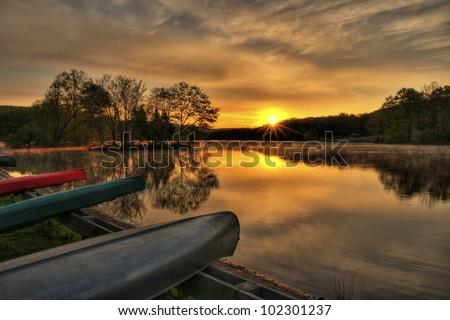 Canoes moored by a beautiful lake at sunrise.