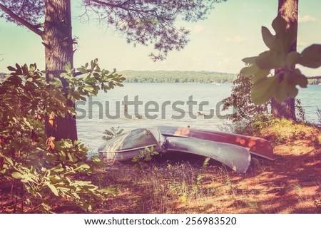 Canoes pulled up on the shore, with kids playing in the lake. Vintage Instagram effect. - stock photo