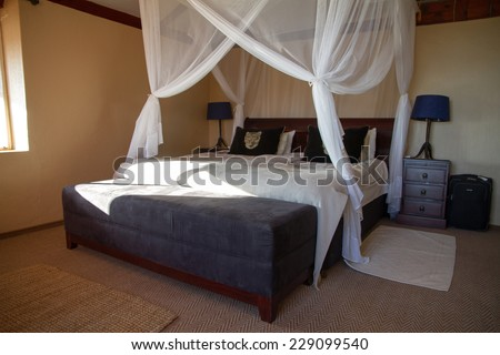 Canopy bed in a comfortable bedroom - stock photo