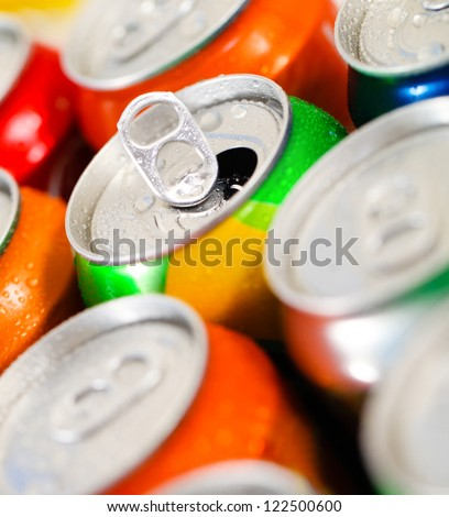 Cans of sweet drinks (or beer). Cooling frozen and with water drops - stock photo