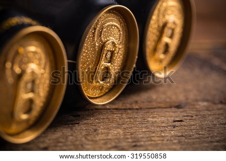 Cans with water drops on wooden background
