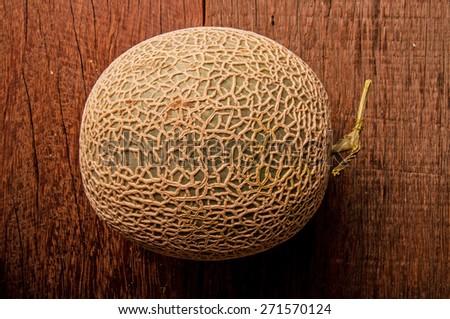 Cantaloupe Melon or Honeydew Melon, Green, Full on Wood Table Background. - stock photo