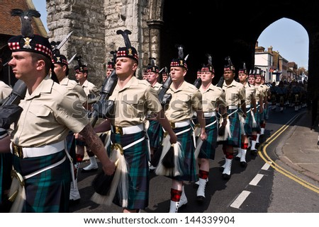 CANTERBURY,UK-JUNE 25:Soldiers from 5SCOTS  with swords drawn march through Canterbury for the final time. The batallion is being restructured due to government cuts. June 25, 2013 Canterbury UK. - stock photo