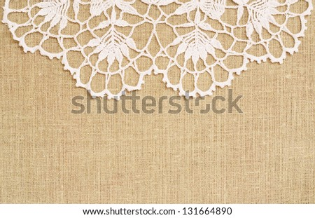 Canvas background with white crochet lace on the top - stock photo