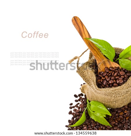 canvas bag with coffee beans decorated with green leaves and a wooden spoon isolated on white background with sample text - stock photo