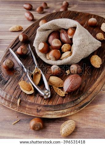 canvas bag with nuts in the shell on a wooden table, with tongs for cracking nuts - stock photo