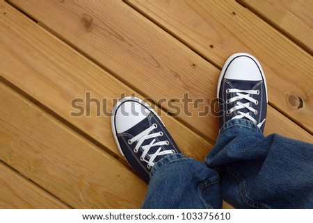 Canvas basket ball shoes on clean wood deck - stock photo
