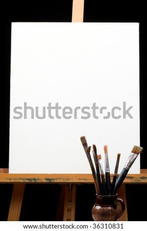 canvas,brushes and easel in black background - stock photo