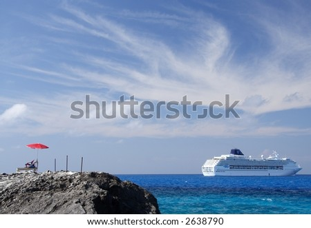 Canvas chair and parasol with a cruiseship in the background - stock photo