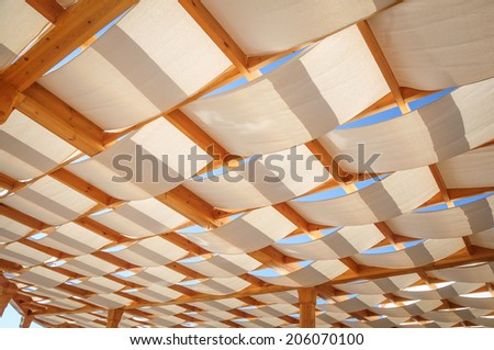 Canvas roof stretched over wooden structure on outdoor patio in a sunny day.  - stock photo
