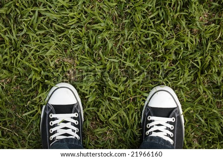 Canvas sneakers on grass, top view, copy space