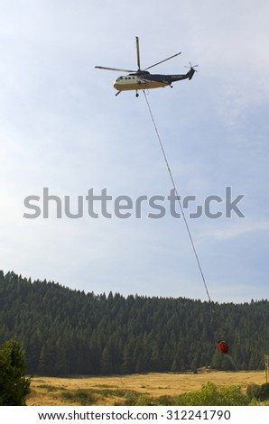 Canyonville, OR, USA - July 31, 2015: Type 2 helicopter comes in for a fill of its water bucket at a wildland fire in Oregon.
