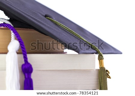 cap and cords on books, achievement and education symbols - stock photo
