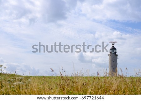 CAP CRIS-NEZ, FRANCE - JULY 21 - Lighthouse on field with yellow grass in summer day