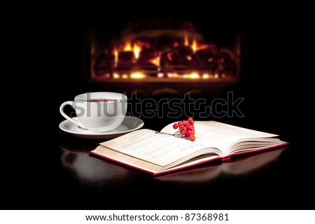 Cap of tea and book on the table top with fireplace in the background.