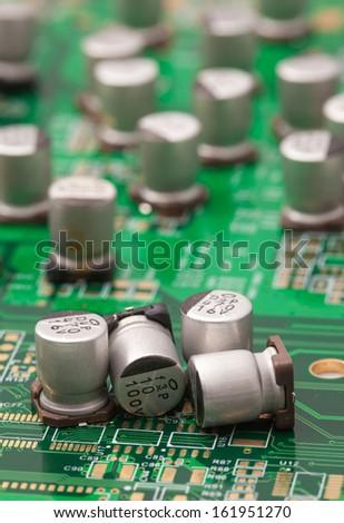 Capacitors on green PCB - stock photo