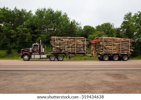 CAPE BRETON, CANADA - 8TH JULY 2015: A Timber Truck on a road in Cape Breton, Nova Scotia showing lots of tree trunks in the trailer.