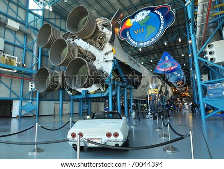 CAPE CANAVERAL, FL- DEC 28: A classic white Corvette and Saturn V rocket displayed in the Apollo/Saturn V Center, at the Kennedy Space Center, NASA in Florida on December 28, 2010. - stock photo