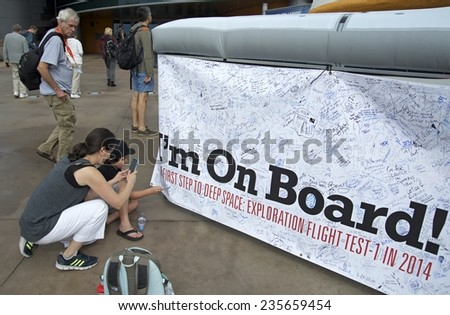 CAPE CANAVERAL, FLORIDA  DECEMBER 5, 2014: Visitors to NASA's Kennedy Space Center signing an I'm On Board sign the day of the launch of spacecraft Orion, the first step to deep space exploration. - stock photo