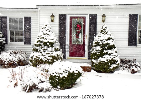 Cape-cod style home with front red door and wreath for the holidays in the midst of a snowstorm. - stock photo