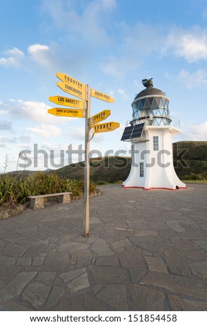 Cape Reinga Lighthouse in New Zealand with signpost. - stock photo