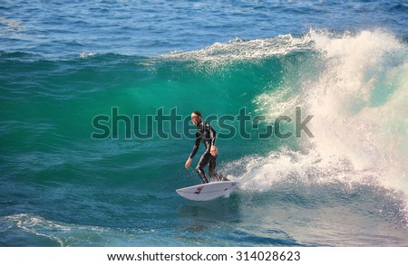 CAPE SOLANDER, AUSTRALIA, AUGUST 9, 2015; a male surfer, catching and surfing the breaks off Cape Solander near Sydney on a beautiful and sunny winter day.