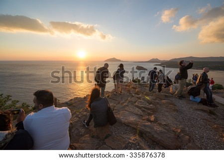 CAPE SOUNION, GREECE - OCTOBER 27, 2015: Many people contemplate the sunset on the Aegean Sea