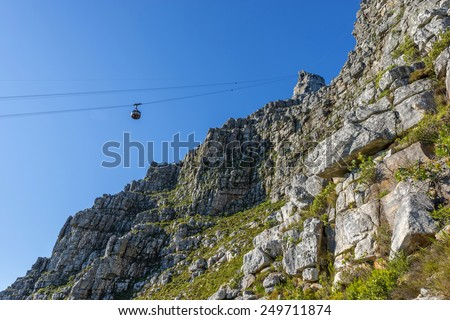 Cape Town's Table Mountain cable car as it takes tourists up to the top and back from the base of the mountain. Table Mountain is one of the seven wonders of the world located in South Africa - stock photo