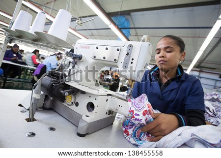 CAPE TOWN, SOUTH AFRICA - AUG 2: A woman creates a new garment in a large clothing factory in Cape Town, South Africa on August 2, 2012 - stock photo