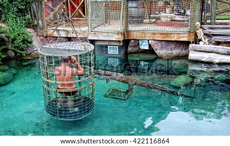 Cape Town, South Africa -December31,2013: A man stands inside of a light fragile cage with large holes & plunges into water with crocodiles. Adrenaline. Stunning South African adventure. Gator show  - stock photo