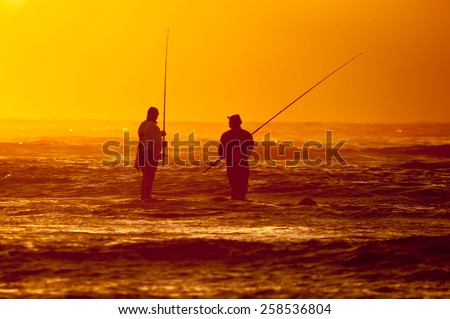 CAPE TOWN, SOUTH AFRICA - DECEMBER 20, 2014: Silhouette of two anglers against sunset at The Strand near Cape Town in the Western Cape Province of South Africa