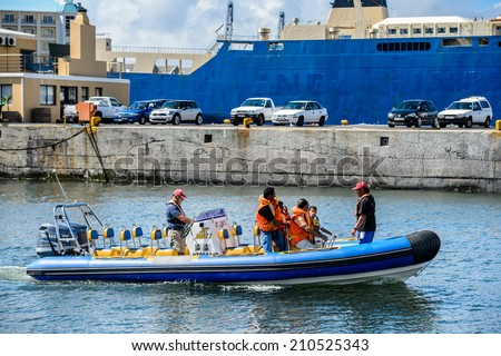 CAPE TOWN, SOUTH AFRICA - FEB 22, 2013: Unidentified people on a boat in the harbor in Cape Town, South Africa. Cape town is the most popular international touristic destination in Africa