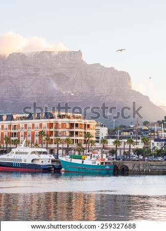 CAPE TOWN, SOUTH AFRICA - FEBRUARY 19, 2015: Waterfront in Cape Town, South Africa, overlooked by Table Mountain at sunset.