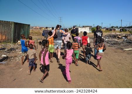CAPE TOWN, SOUTH AFRICA - JANUARY 26, 2013: African children accompaniyng European tourists, walking through informal settlement Langa town ship - stock photo