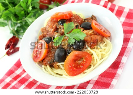 Capellini with tomatoes, anchovies, capers and olives - stock photo