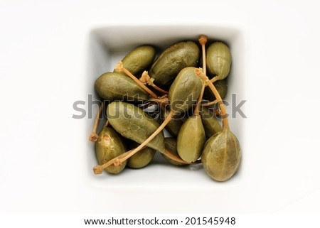 caper berries isolated in white dish - stock photo