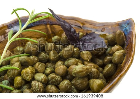 Capers in the bowl with rosemary - stock photo