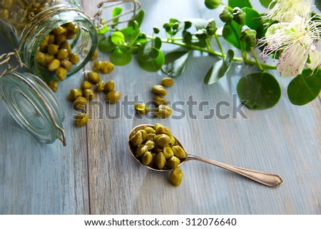 Capers pickled with plant and caper plant flower on vintage spoon - stock photo