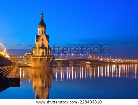Capital of Ukraine - Kyiv. Church of Saint Nicholas on the water, old embankment and Havanskyi Bridge in Kiev at night. - stock photo