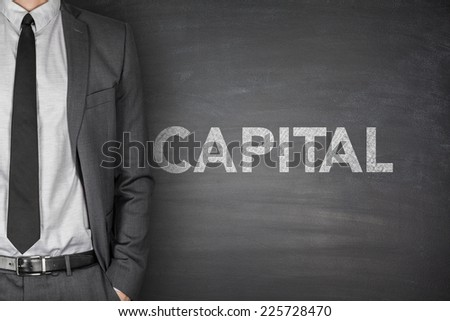 Capital word on black blackboard with businessman - stock photo