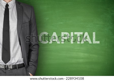 Capital word on green blackboard with businessman - stock photo