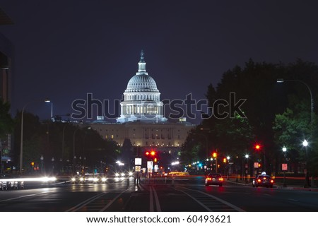 Capitol seen from Pennsylvania Avenue. Night time with traffic rushing by.
