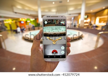 "CAPITOLA, CALIFORNIA - JULY 13, 2016: The hit augmented reality smartphone app ""Pokemon GO"" shows a Pokemon encounter at a mall fountain in the real world.  - stock photo"