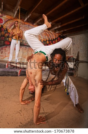 Capoeira expert working with partner in handstand - stock photo
