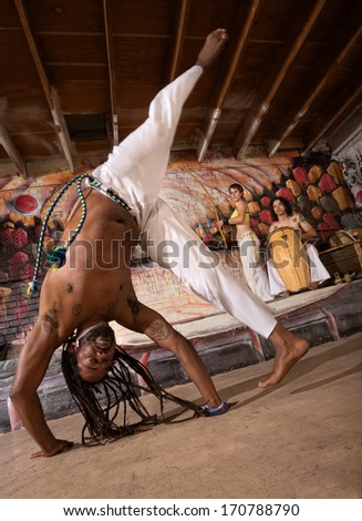 Capoeira man performing a cartwheel flip indoors - stock photo