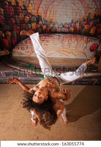 Capoeira performers practicing back shoulder throwing indoors - stock photo