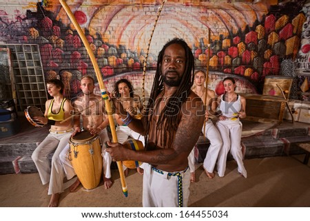 Capoeira teacher with dreadlocks and students playing music  - stock photo